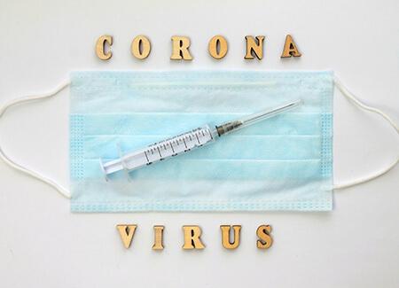 Scritta coronavirus con siringa e mascherina