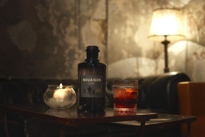 bottiglia di gin con bicchiere con cocktail negroni distribuito da mixer cocktails