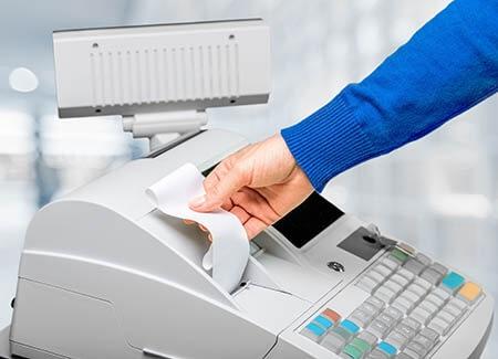 mano che strappa scontrino dal registratore di cassa